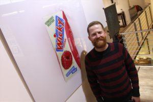 Künstler Martin Wanka neben der Abbildung einer holländischen Getränkepackung. (Foto: Björn Othlinghaus)